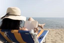 mujer leyendo un libro sobre tecnología en la playa
